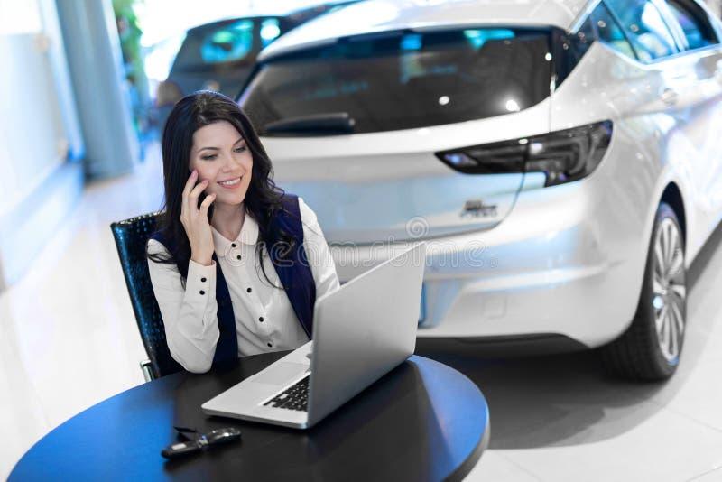 Retrato del agente de seguro smilling hermoso que se sienta y que habla en el tel?fono cerca del nuevo coche imágenes de archivo libres de regalías