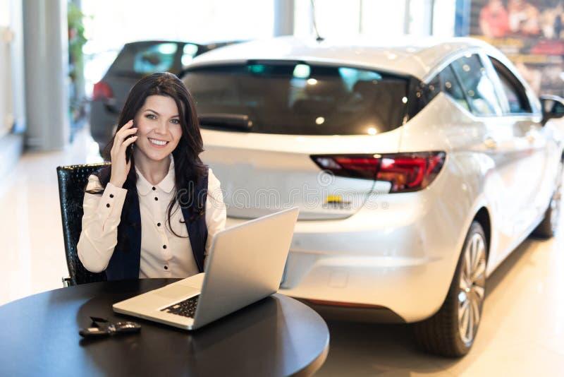 Retrato del agente de seguro smilling hermoso que se sienta y que habla en el tel?fono cerca del nuevo coche foto de archivo