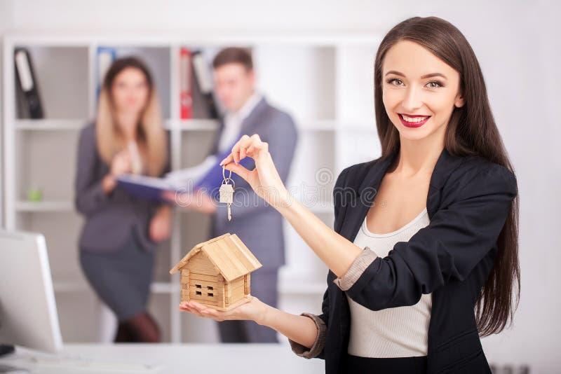 Retrato del agente inmobiliario con la familia que consigue el nuevo hogar Negocios imagen de archivo
