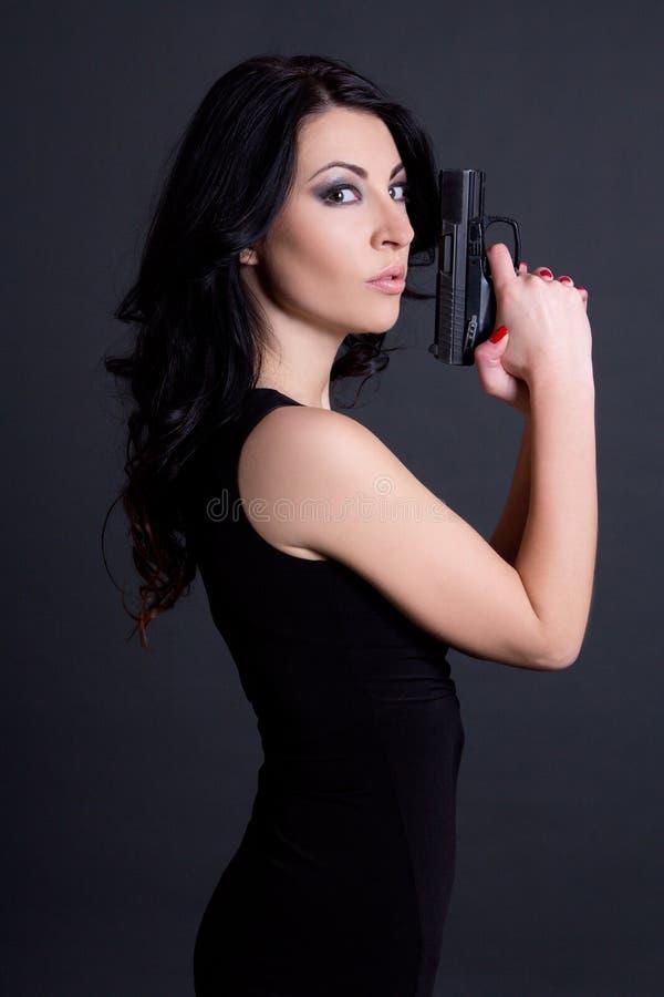 Retrato del agente secreto de la mujer atractiva que presenta con el arma sobre gris fotos de archivo