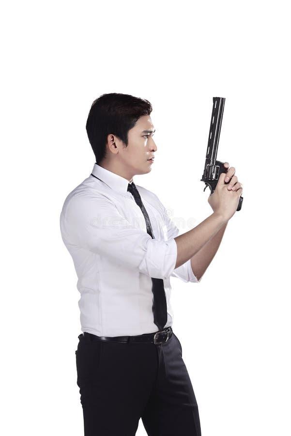 Retrato del agente secreto que sostiene un arma fotografía de archivo