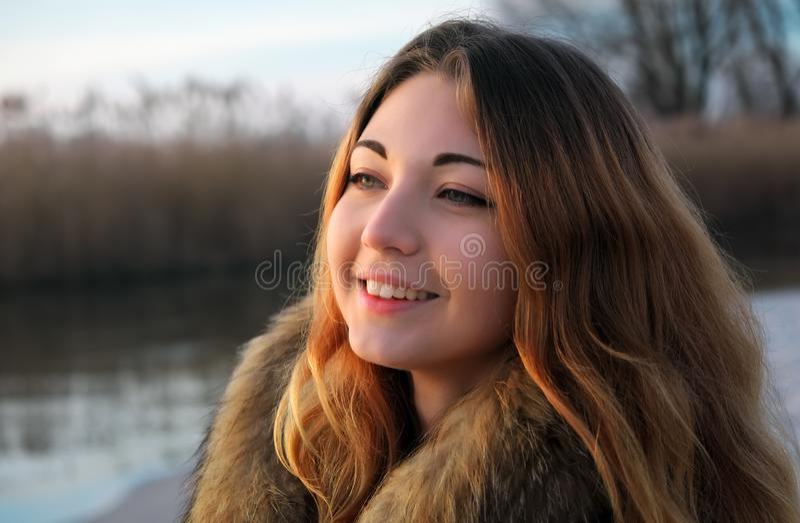 Retrato del aire libre de la muchacha sonriente hermosa joven con las mejillas rojas en invierno cerca del lago congelado foto de archivo libre de regalías