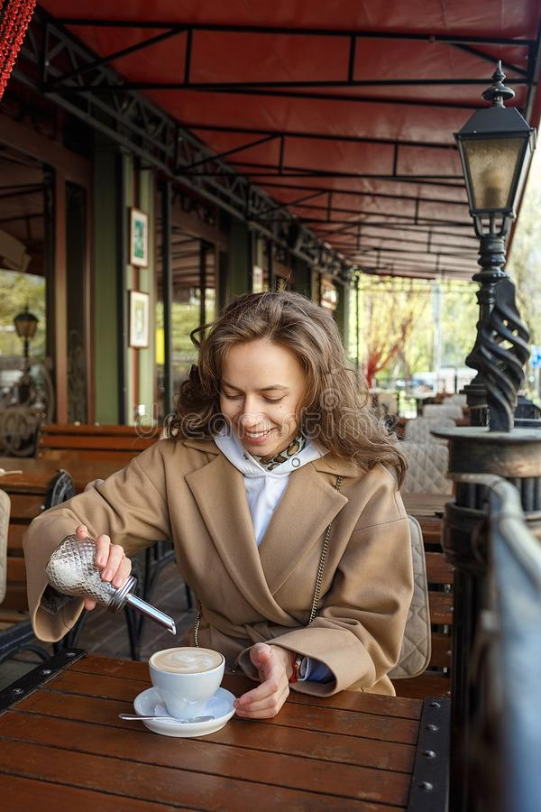 Retrato del aire libre de la muchacha sonriente joven que lleva la capa beige que añade el azúcar en una taza de café mientras qu foto de archivo libre de regalías