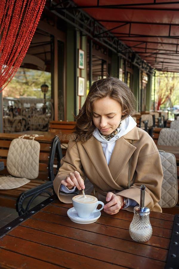 Retrato del aire libre de la muchacha sonriente joven que lleva el caf? de consumici?n de la capa beige en el az?car stiring del  fotos de archivo libres de regalías