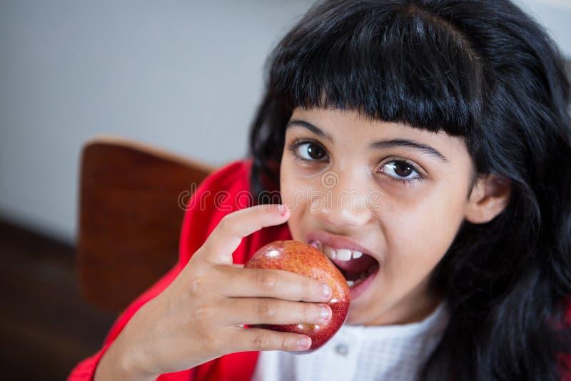 Retrato del alto ángulo de la muchacha que come la manzana fresca fotografía de archivo libre de regalías