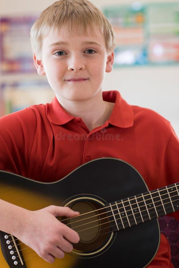 Retrato del alumno masculino de la High School secundaria que toca la guitarra fotografía de archivo
