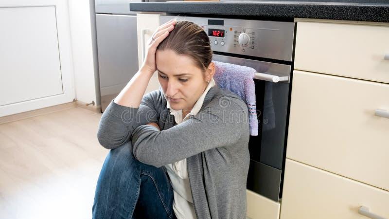 Retrato del ama de casa joven que sufre de la depresión que se sienta en piso en la cocina foto de archivo
