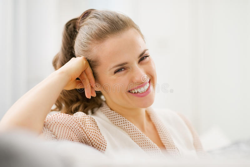 Retrato del ama de casa joven sonriente que se sienta en el diván foto de archivo