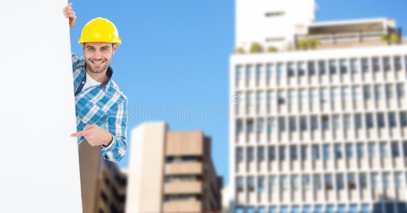 Retrato del arquitecto de sexo masculino sonriente que señala en la cartelera en blanco contra edificios imagen de archivo libre de regalías