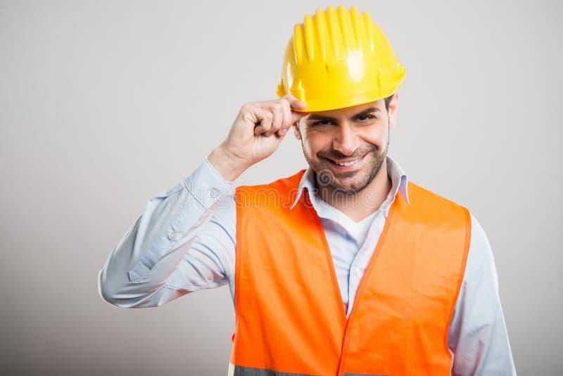 Retrato del arquitecto joven que sostiene su casco como saludo foto de archivo libre de regalías