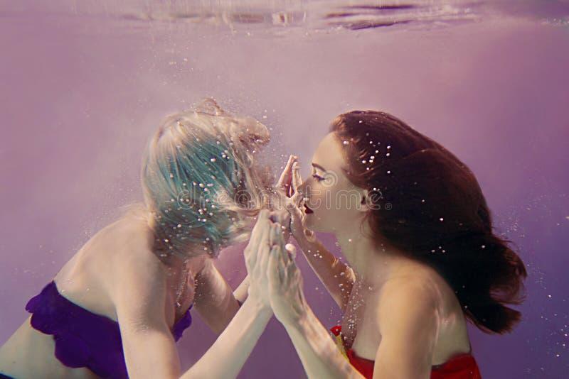 Retrato del arte de dos muchachas bonitas hermosas que se detienen manos subacuático fotos de archivo