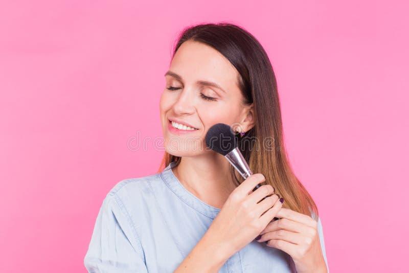 Retrato del artista de maquillaje con el cepillo en un fondo rosado fotos de archivo