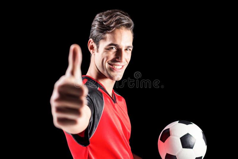 Retrato del atleta de sexo masculino que lleva a cabo fútbol y que muestra los pulgares para arriba fotografía de archivo libre de regalías