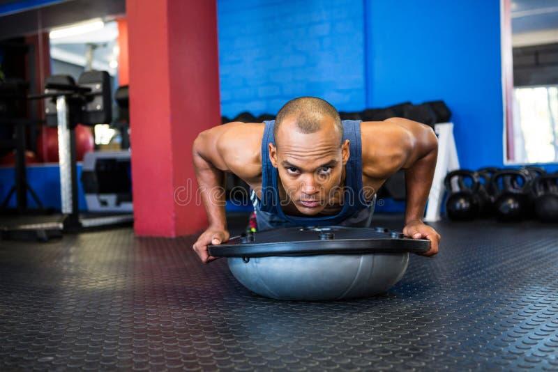 Retrato del atleta de sexo masculino severo con la bola de BOSU en gimnasio foto de archivo