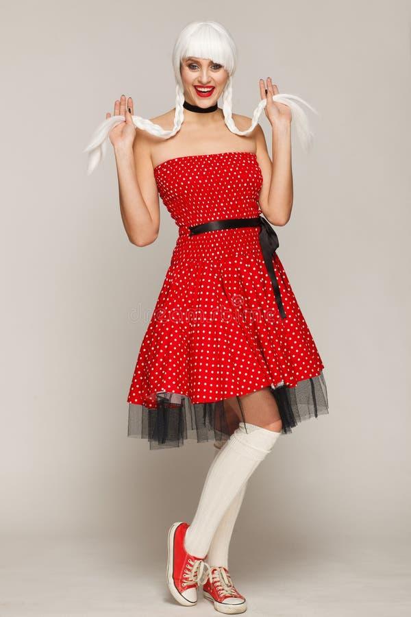 Retrato del awoman en una peluca blanca, un vestido rojo y zapatillas de deporte Sesi?n de foto del estudio imágenes de archivo libres de regalías