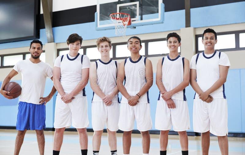 Retrato del baloncesto masculino Team With Coach On Court de la High School secundaria foto de archivo libre de regalías