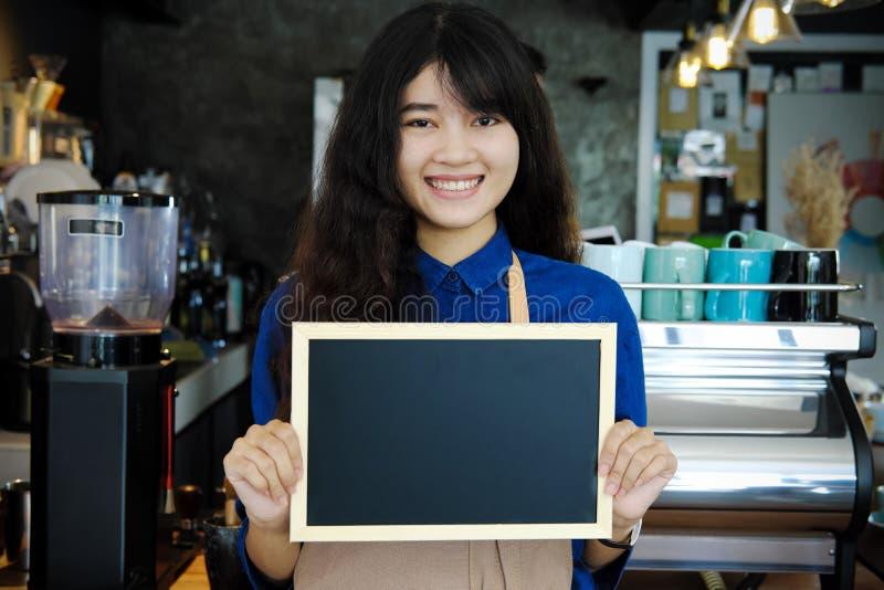 Retrato del barista asiático que lleva a cabo el menú en blanco de la pizarra en coffe imagenes de archivo
