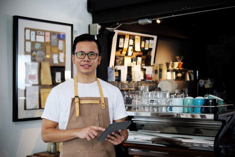 Retrato del barista asiático que sostiene la tableta digital en el contador en c fotos de archivo