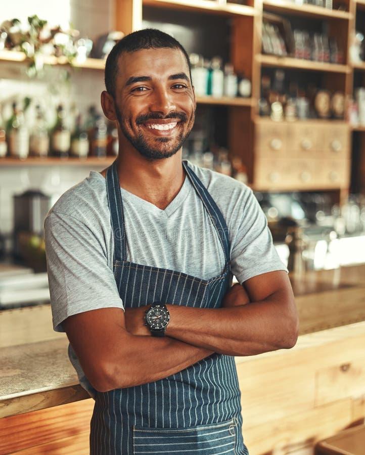 Retrato del barista masculino confiado en el contador en café imágenes de archivo libres de regalías