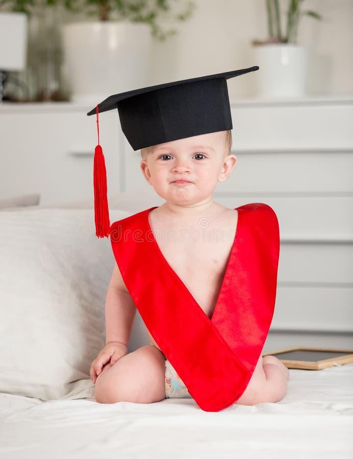 Retrato del bebé adorable en sitti del casquillo y del cuello de la graduación imagenes de archivo
