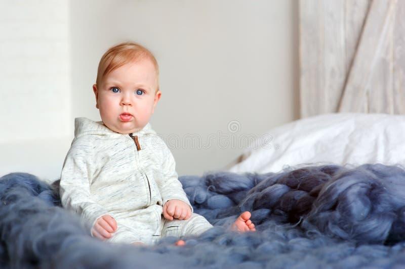 Retrato del bebé de 8 meses lindo que se sienta en la cama en la manta hecha punto de gran tamaño fotografía de archivo libre de regalías