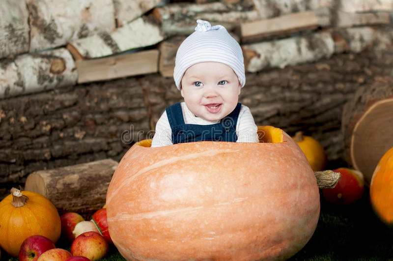 Retrato del bebé divertido en calabaza grande fotos de archivo