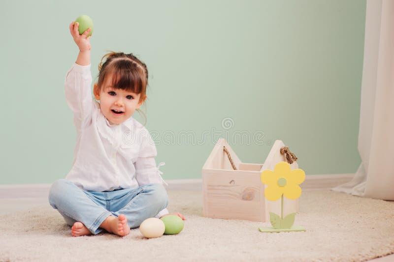 Retrato del bebé feliz lindo que juega con las decoraciones de pascua imagenes de archivo