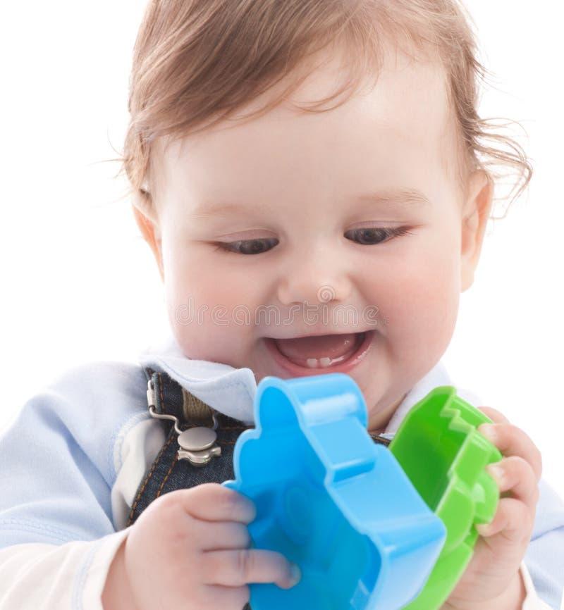 Retrato del bebé feliz que juega con los juguetes fotos de archivo