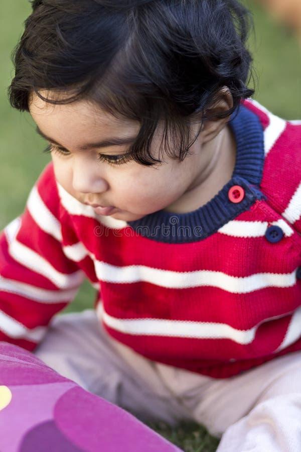 Retrato del bebé hermoso en el césped foto de archivo