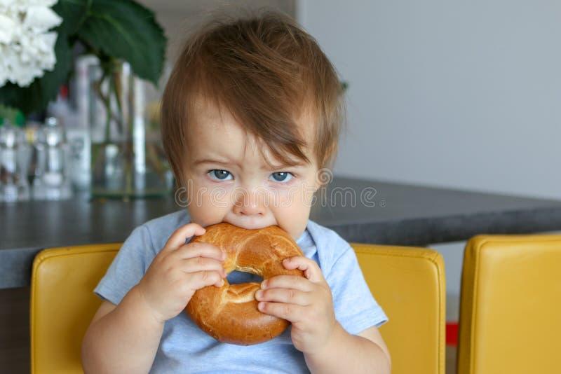 Retrato del bebé lindo con el corte de pelo elegante que sostiene y que come el panecillo grande que se sienta en cocina amarilla imágenes de archivo libres de regalías