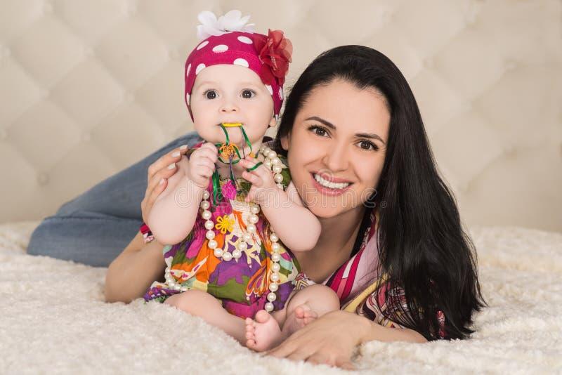 Retrato del bebé lindo con la madre en la cama, dentro fotografía de archivo libre de regalías
