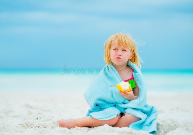 Retrato del bebé que come la pera en la playa imagen de archivo libre de regalías
