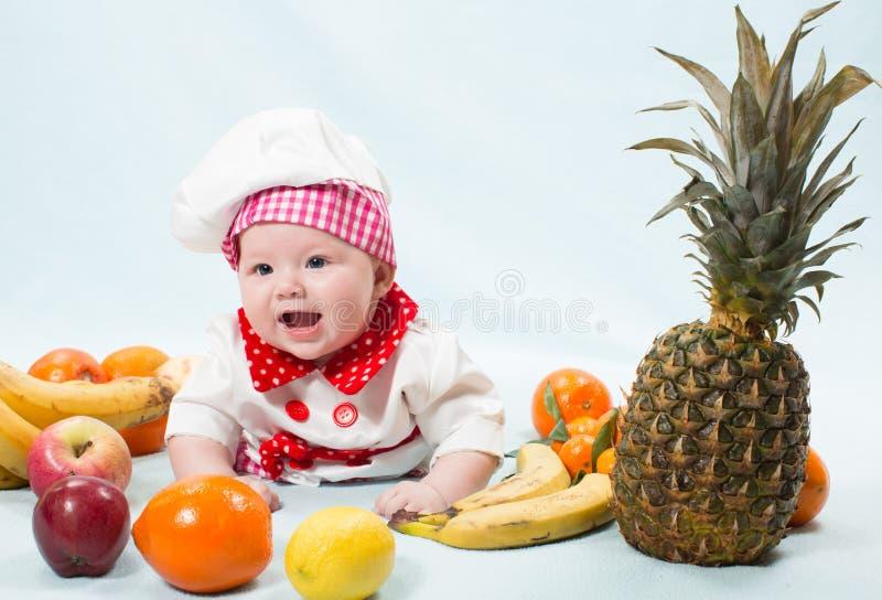 Retrato del bebé sonriente que desgasta un sombrero del cocinero rodeado por las frutas fotos de archivo