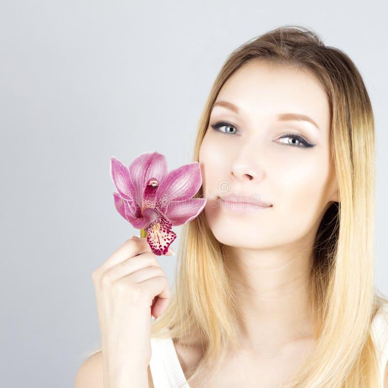 Retrato del blonde sonriente con la flor rosada Cara de la belleza de la mujer foto de archivo