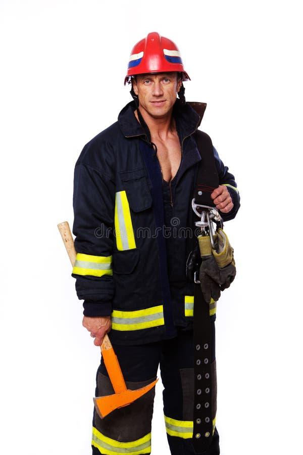Retrato del bombero que presenta en el fondo blanco foto de archivo