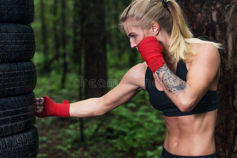 Retrato del boxeador de la muchacha que hace el retroceso del gancho que se resuelve al aire libre fotos de archivo libres de regalías