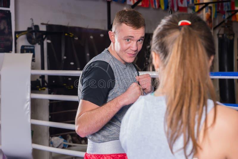 Retrato del boxeador de sexo masculino joven en el entrenamiento de la ropa de deportes con la hembra fotos de archivo