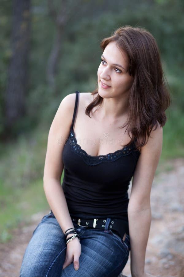 Retrato del brunette que se sienta al aire libre imagenes de archivo
