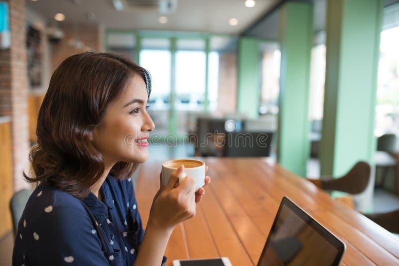 Retrato del café de consumición de la mujer asiática joven atractiva fotografía de archivo