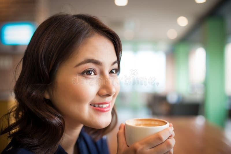 Retrato del café de consumición de la mujer asiática joven atractiva imágenes de archivo libres de regalías