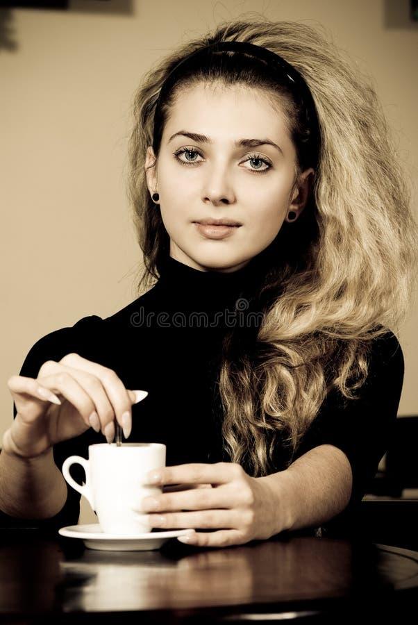Retrato del café de consumición de la mujer joven foto de archivo