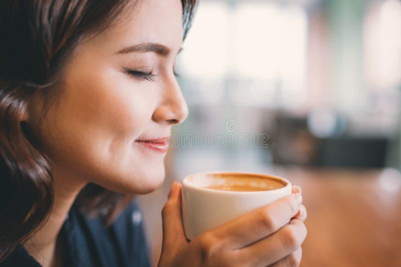 Retrato del café de consumición de la mujer asiática joven atractiva foto de archivo