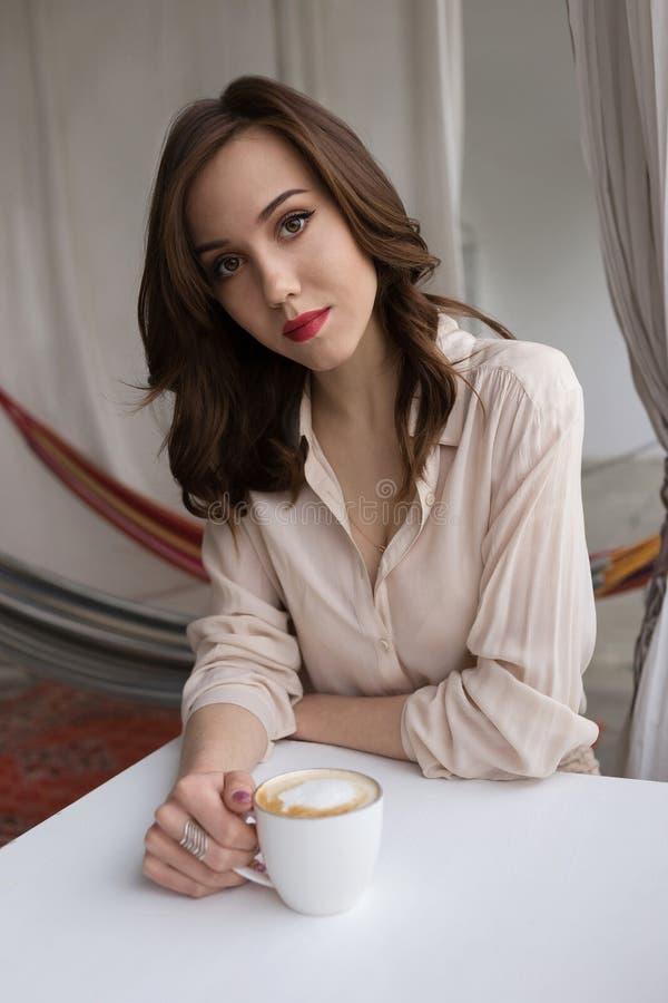 Retrato del café de consumición de la mujer sensual joven en un mirador del café Concepto de relajaci?n y de ocio de la ciudad imagenes de archivo