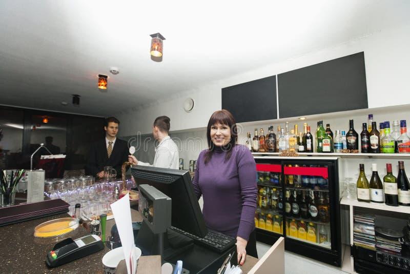 Retrato del cajero femenino con el encargado y el camarero en el contador de la barra foto de archivo