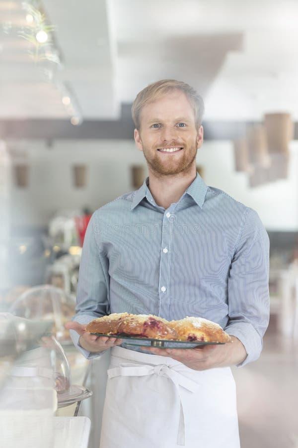 Retrato del camarero joven sonriente que celebra el pan fresco en bandeja en el restaurante fotos de archivo