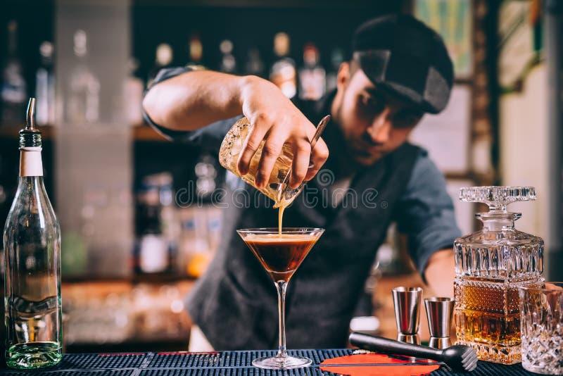 retrato del camarero que crea los cócteles en la barra Ciérrese para arriba de la preparación de la bebida alcohólica fotografía de archivo libre de regalías