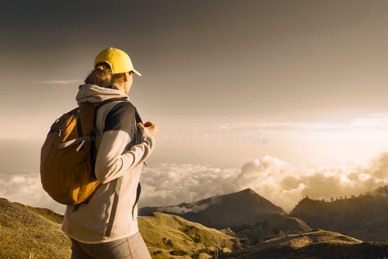 Retrato del caminante de la mujer joven con el backpacker que camina en el alto mou fotos de archivo