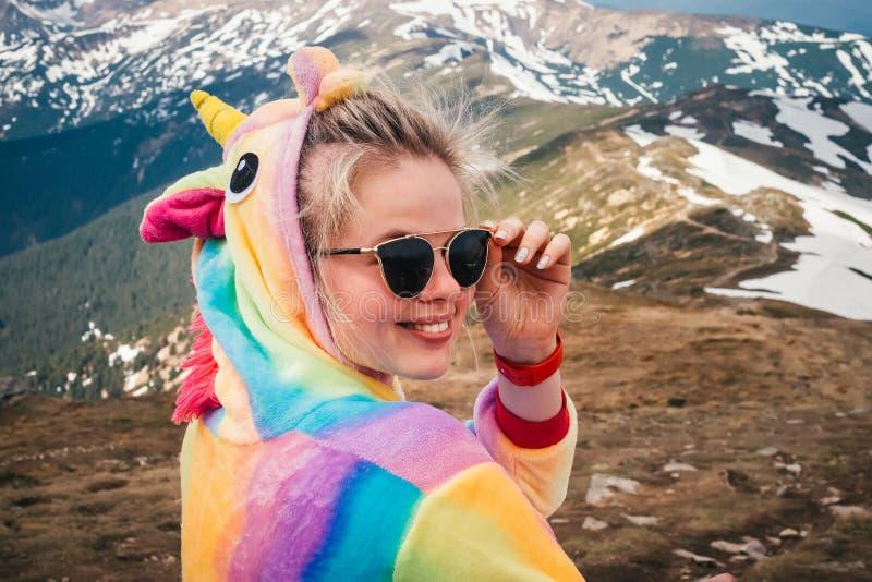 Retrato del caminante femenino en un traje del unicornio en montañas foto de archivo libre de regalías