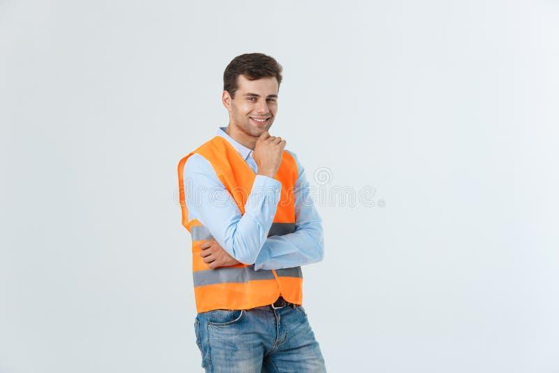 Retrato del capataz joven feliz con el chaleco anaranjado aislado sobre el fondo blanco foto de archivo