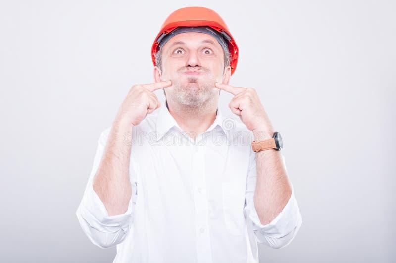 Retrato del casco de protección que lleva del contratista que hace gesto tonto imágenes de archivo libres de regalías